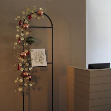Capsule frame gedecoreerd met gouden glitterrank en kerstballen.