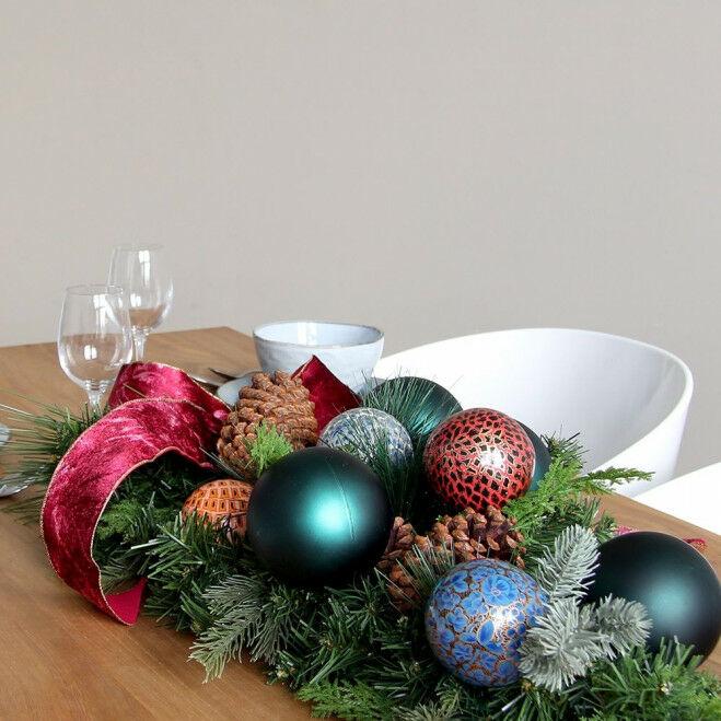 Tafeldecor van gemengd kunstgroen met handgemaakte kerstballen en lint